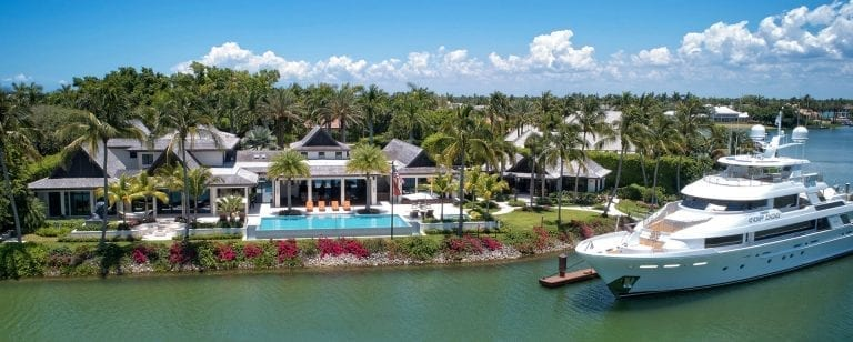 Large home with infinity pool and large yacht docked in front